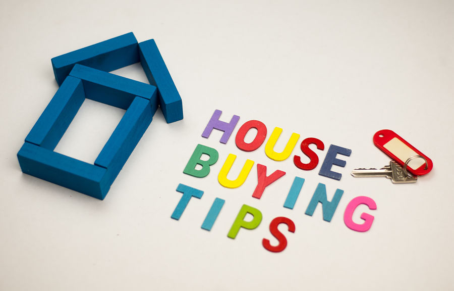 House model and wooden alphabet with text house buying tips